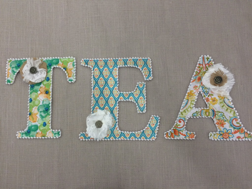 letters covered in fabric [if you have a flat letter, this will be your final step - before gluing the fabric, fold over your hem and iron in place, continuing this around the entire letter make more, deeper cuts if required to create a neat line around the fabric.